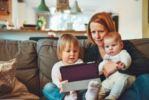 En mor som sitter og leser for barna sine